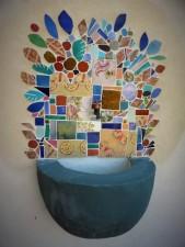 Mosaïque autour d'un robinet et vasque dans un jardin.
